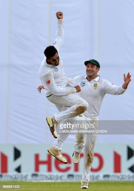 South Africa's Tabraiz Shamsi celebrates with teammate Dean Elgar after dismissing Sri Lanka's batsman Niroshan Dickwella during the first day of the...