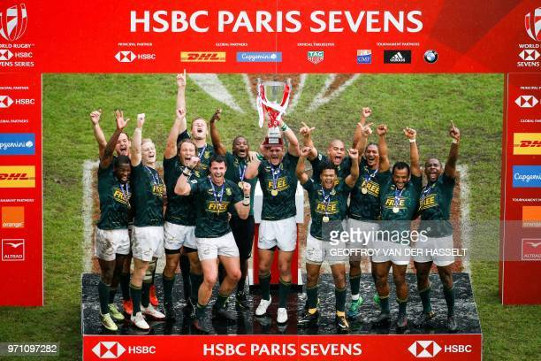 South Africa's team holds the trophy after winning the final of the Men cup rugby union 7s game between South Africa and England on the third day of...