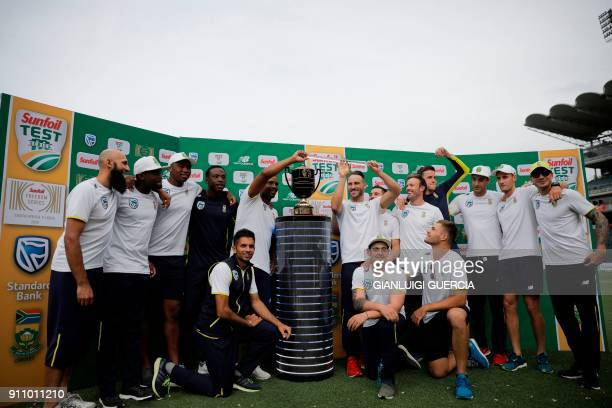 South Africa's team poses with the trophy after winning the threematch series 21 after the fourth day of the third Test match between South Africa...