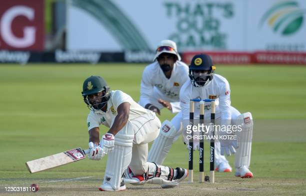 South Africa's Temba Bavuma is watched by Sri Lanka's wicketkeeper Niroshan Dickwella as he plays a shot during the second day of the first Test...