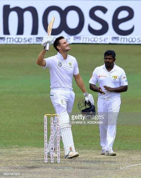 South Africa's Theunis de Bruyn celebrates after scoring 100 runs as Rangana Herath looks on during the fourth day of the second Test match between...