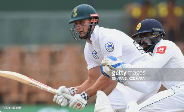 South Africa's Theunis de Bruyn plays a shot as Sri Lanka's wicketkeeper Niroshan Dickwella looks on during the fourth day of the second Test match...