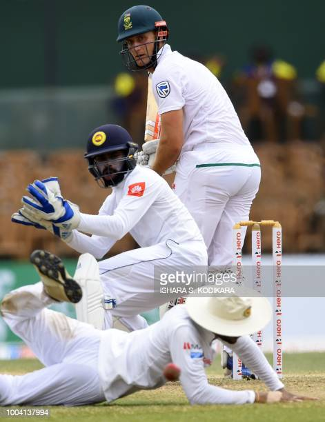 South Africa's Theunis de Bruyn plays a shot as Sri Lanka's wicketkeeper Niroshan Dickwella looks on during the fourth day of their second Test match...