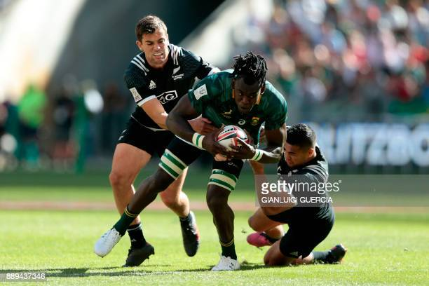 South Africa's Tim Agaba is tackled by New Zealand Regan Ware during their semifinal match on the second day of the World Rugby Sevens Series at Cape...