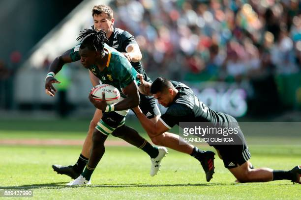 South Africa's Tim Agaba is tackled by New Zealand's Regan Ware during their semifinal match on the second day of the World Rugby Sevens Series at...