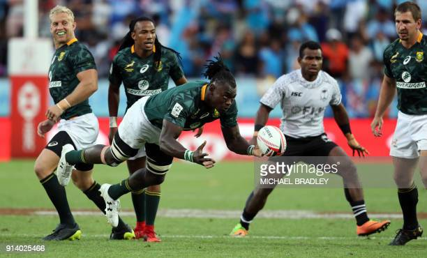 South Africa's Tim Agaba passes the ball off during the final gold medal match at the World Rugby Sevens Series between Fiji and South Africa at...