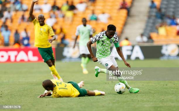 South Africa's Tiyani Mabunda is tackled by Nigeria's captain Ahmed Musa during the African Cup of Nations qualifier match between South Africa and...