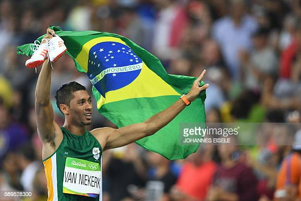 South Africa's Wayde van Niekerk celebrates winning the Men's 400m Final during the athletics event at the Rio 2016 Olympic Games at the Olympic...