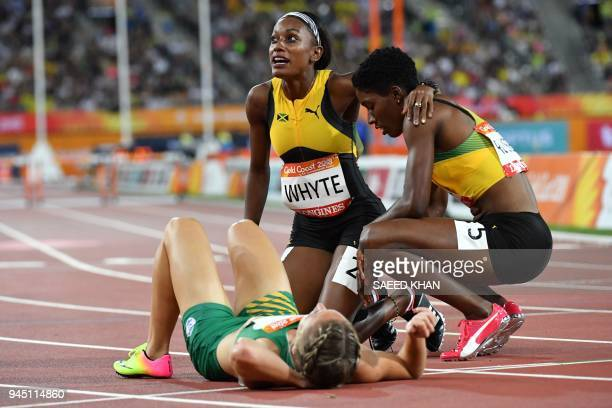 South Africa's Wenda Nel lies on the track as Jamaicas Janieve Russell celebrates with Jamaicas Ronda Whyte after Russell won the athletics women's...