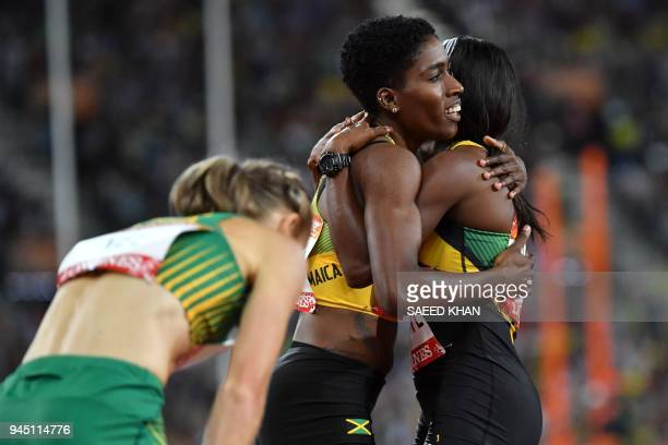 South Africa's Wenda Nel reacts as Jamaicas Janieve Russell celebrates with Jamaicas Ronda Whyte after Russell won the athletics women's 400m hurdles...
