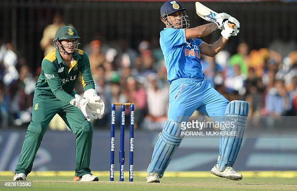 South Africa's wicketkeeper Quinton de Kock looks on as India's captain Mahendra Singh Dhoni plays a shot during the second one day international...