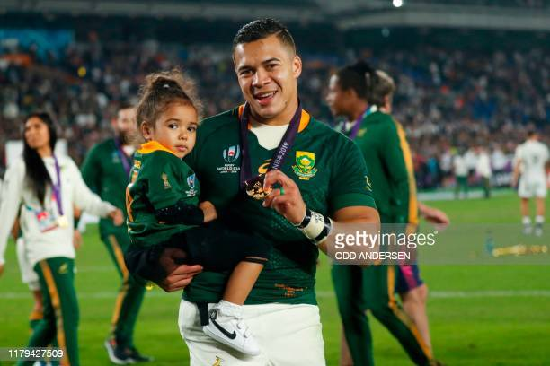 South Africa's wing Cheslin Kolbe carries his daughter after winning the Japan 2019 Rugby World Cup final match between England and South Africa at...