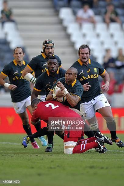South Africa's wing Cornal Hendricks is tackled by Wales' hooker Ken Owens during the second rugby Test match between South Africa and Wales at...