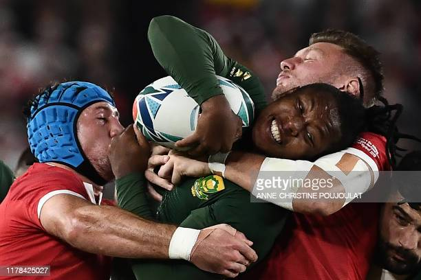 South Africa's wing S'Busiso Nkosi is tackled by Wales' flanker Justin Tipuric and Wales' flyhalf Dan Biggar during the Japan 2019 Rugby World Cup...
