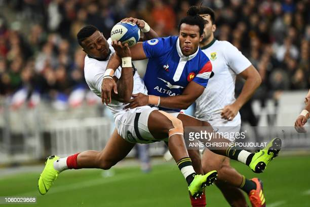 South Africa's winger Aphiwe Dyantyi jumps for the ball with France's winger Teddy Thomas during the international rugby union test match between...