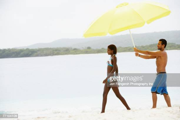 South American man holding umbrella for woman at beach