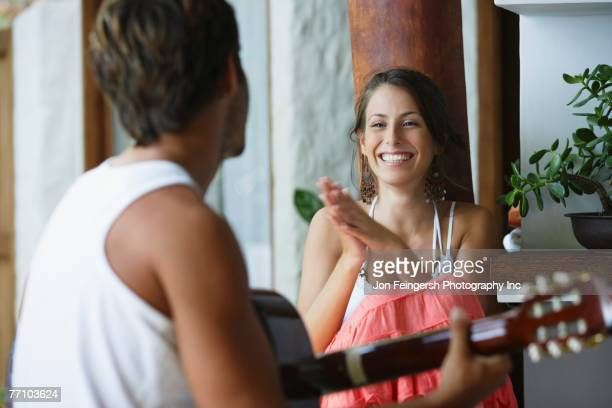 South American man playing guitar for girlfriend