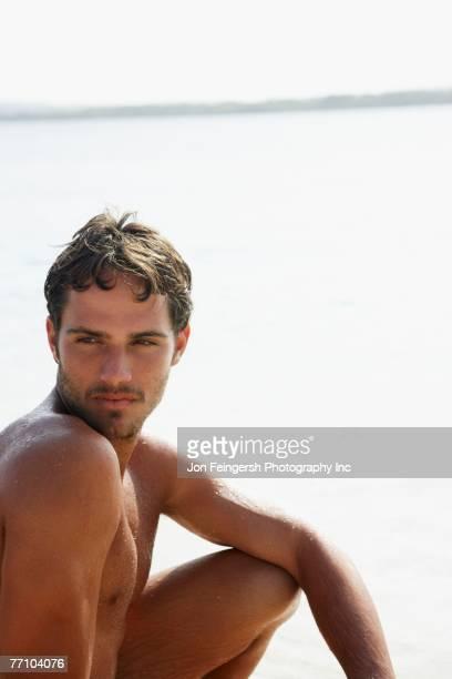 South American man sitting on beach