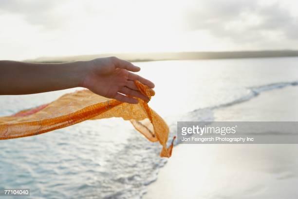 South American woman holding sarong at beach