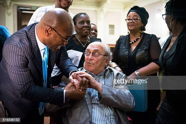 South Aricas minister of Arts and Culture Nathi Mthethwa shakes hands with one of the defendants from the Rivonia Trial Denis Goldberg during the...