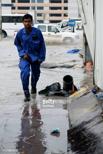 South Asian migrant worker navigates his way through again puddle in Doha, Qatar. Rain lashed down on Qatar on 20 October 2018 causing the roads to...