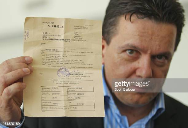 South Australian Federal Senator Nick Xenophon holds up his deportation notice as he arrives at Adelaide Airport after his deportation from Malaysia...