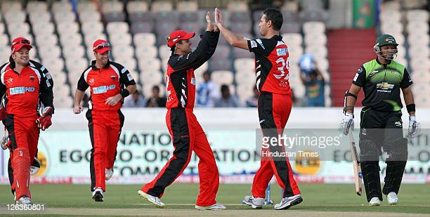 South Australian Redbacks bowler Shaun Tait celebrates with team members after he bowled Warriors batsman Ashwell Prince during the Champions League...