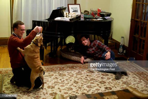 South Bend Mayor Pete Buttigieg watches as his husband Chasten Glezman plays with their dog Buddy at their home on Tuesday December 18 2018 in South...
