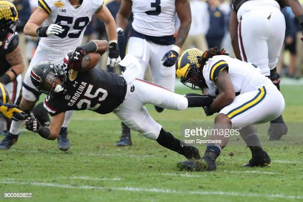 South Carolina Gamecocks running back AJ Turner is tackled by Michigan Wolverines linebacker Devin Bush during the 2018 Outback Bowl between the...