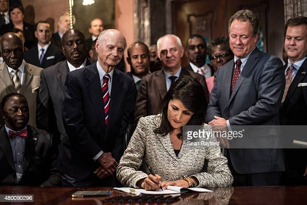 South Carolina Gov Nikki Haley signs a bill to remove the Confederate battle flag from the state house grounds July 9 2015 in Columbia South Carolina...