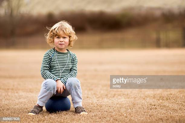 USA, South Carolina, Greenville County, Greenville, Boy (2-3) with ball in soccer field