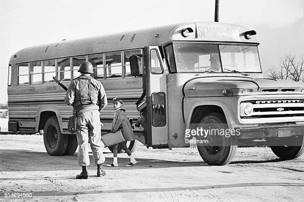 South Carolina National Guardsman meets a school bus as it arrives with African American students at the Lamar School. A little girl watches the...