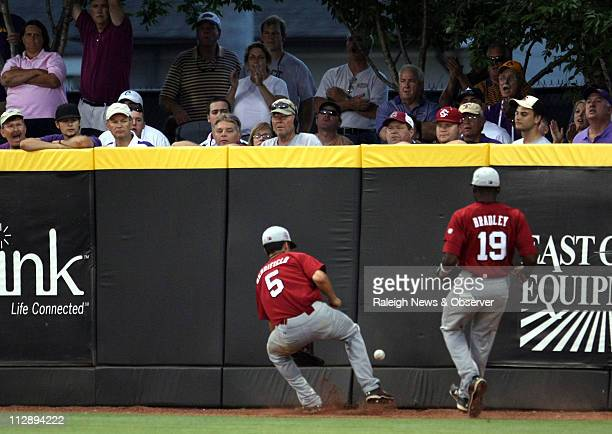 South Carolina outfielders Whit Merrifield and Jackie Bradley Jr field a ball against the fence in the sixth inning against East Carolina ECU...