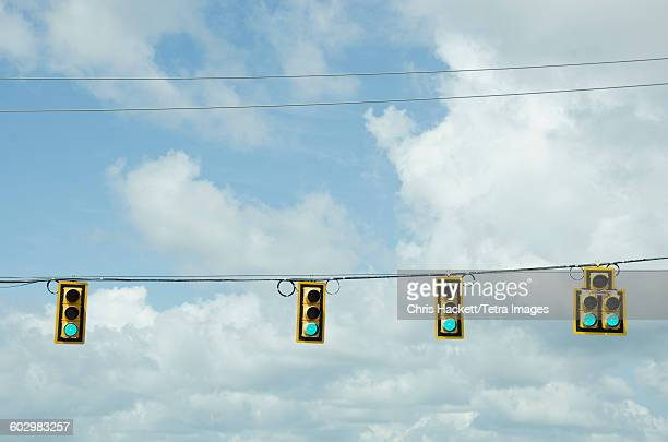 USA, South Carolina, Road signals on cable against cloudy sky