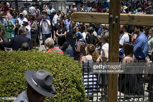 A South Carolina State Trooper walks past as people gather for a vigil while services are held at Morris Brown AME Church June 18 2015 in Charleston...