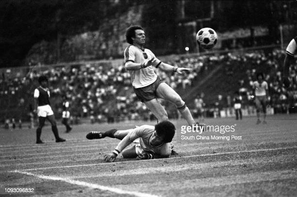 South China goalkeeper Lee Ahkau dives forward and succeeds in blocking a shot from Urban Services' David Brand during a First Division league match...