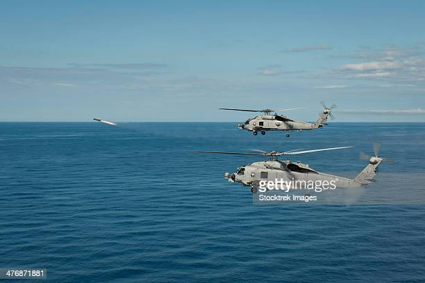 South China Sea, May 18, 2013 - Two MH-60R Sea Hawk helicopters launch AGM-114 hellfire missiles during a live fire exercise.