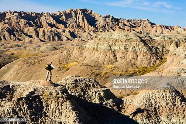 USA, South Dakota, Badlands NP, mature male hiker reading map