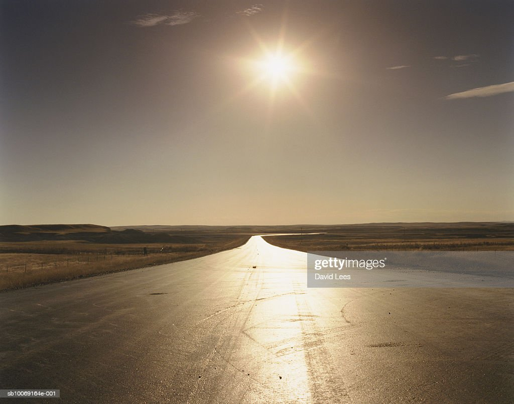 USA, South Dakota, Badlands, Sun reflecting on rural road : Stockfoto