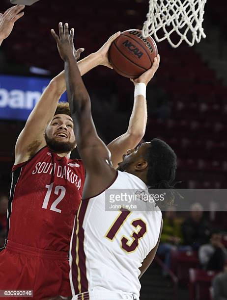 South Dakota Coyotes forward Trey BurchManning goes up for a shot on Denver Pioneers forward CJ Bobbitt during the first half January 4 2017 at...