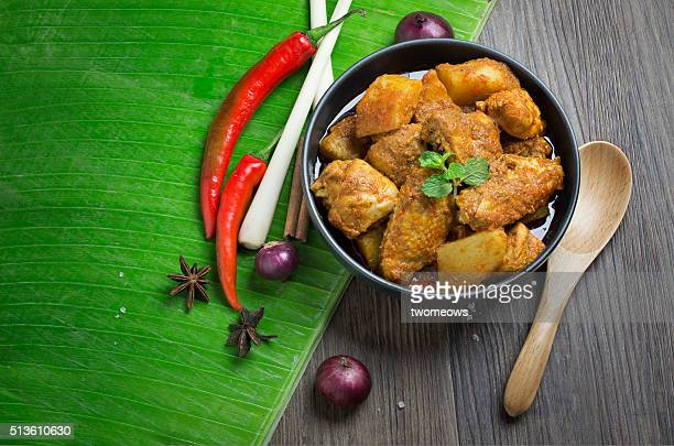 South east asia style curry chicken in bowl on banana leaf. Top view. Text space image.