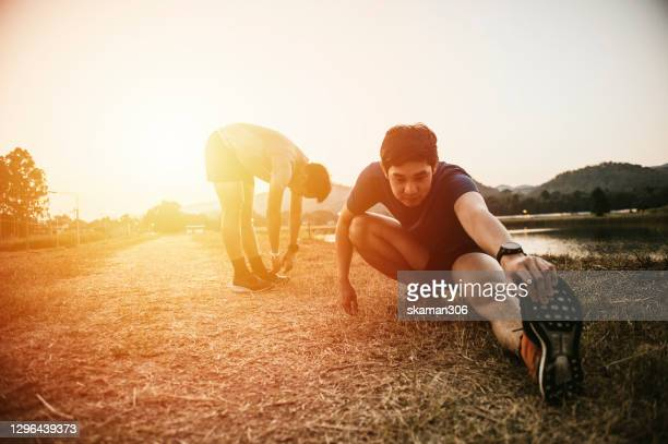 south east asian couple sport man very exhausted and stretching after finish running outdoor 10 km - shooting at goal stock pictures, royalty-free photos & images