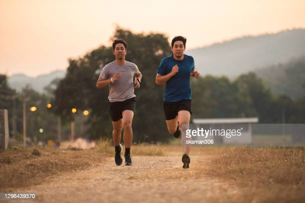 south east asian couple sport man workout and jogging outdoor until the sun goes down - shooting at goal stock pictures, royalty-free photos & images
