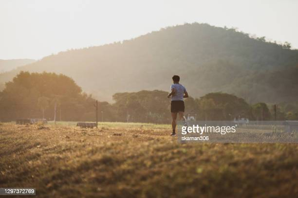 south east asian sport man feeling motivate to finish running outdoor 10 km - shooting at goal stock pictures, royalty-free photos & images