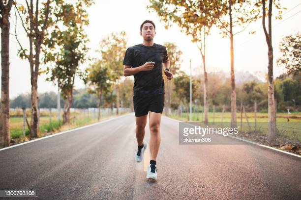 south east asian sport man jogging outdoor at countryside - shooting at goal stock pictures, royalty-free photos & images