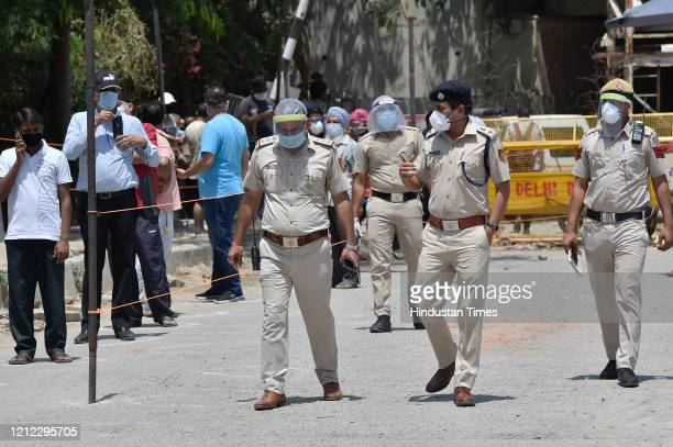 South East Delhi, RP Meena, along with other police officers on an inspection as people wait to buy alcohol outside a liquor shop in, Sri Niwaspuri,...