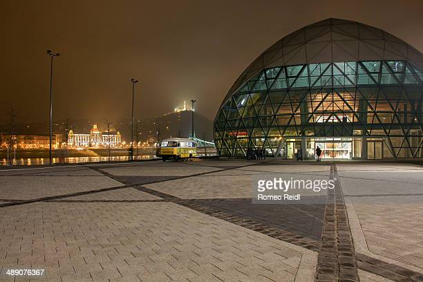 South entrance of the Balna building at night with the Hotel Gellert and the Citadell in the background. This is a colossal glass and metal structure...