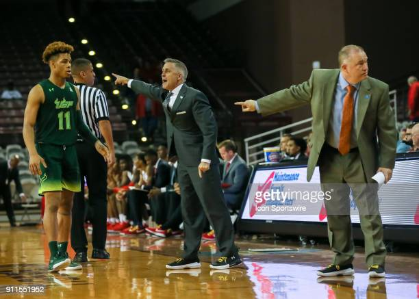 South Florida Bulls head coach Brian Gregory and South Florida Bulls assistant coach Tom Herrion talk to players during the college basketball game...