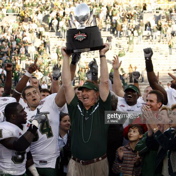 South Florida head Coach Jim Leavitt hoists the PapaJohnscom Bowl Trophy as his team cheers him on after Saturday's game against East Carolina at...