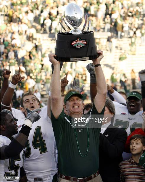 South Florida head coach Jim Leavitt hoists the PapaJohnscom Bowl Trophy over his head after Saturday's victory over East Carolina at Legion Field in...